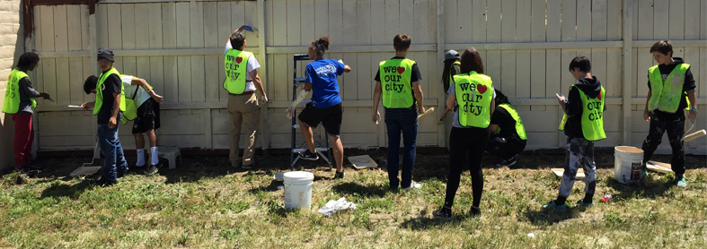 "Members of the ""we love our city"" team help clean up a neighborhood by adding a fresh coat of paint to a fence."